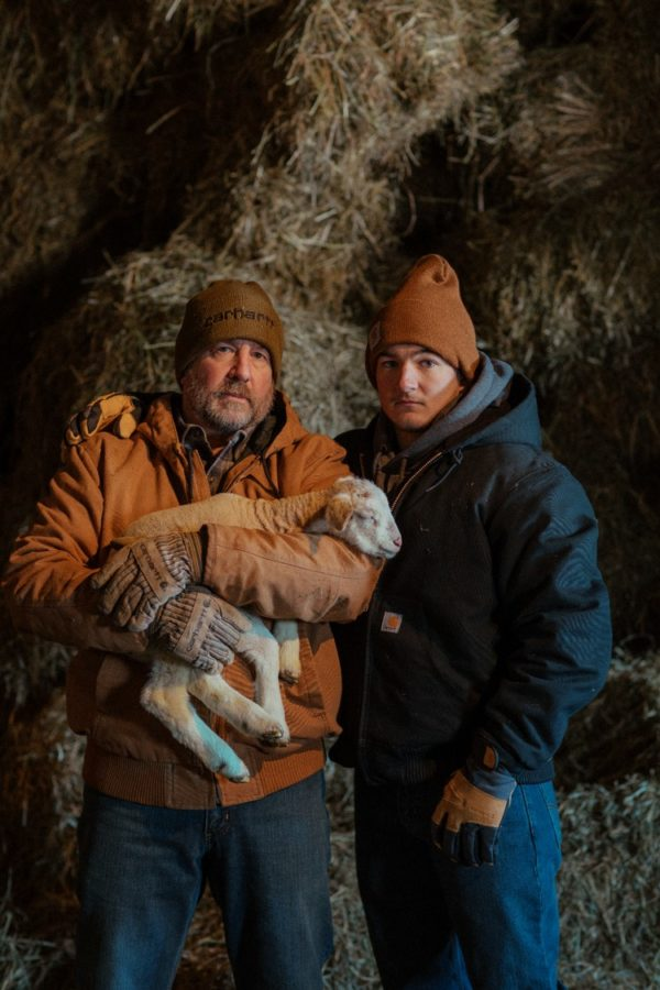 2 men wearing Carhartt Outerwear and attending to a Lamb